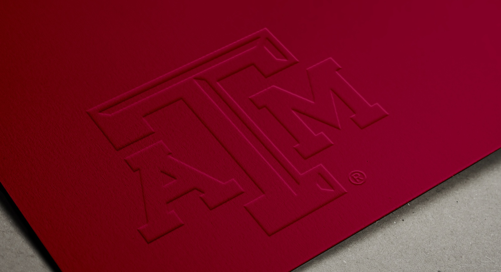 Maroon business card with embossed A&M logo
