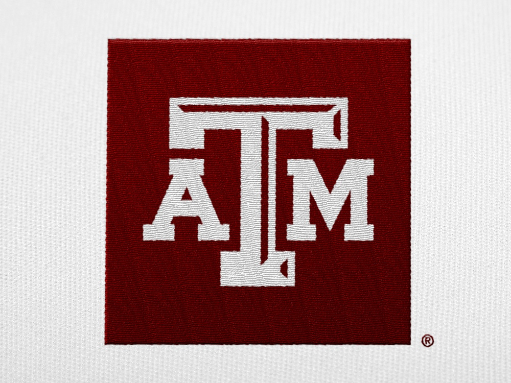 A white A&M logo with a maroon box embroidered on a white shirt