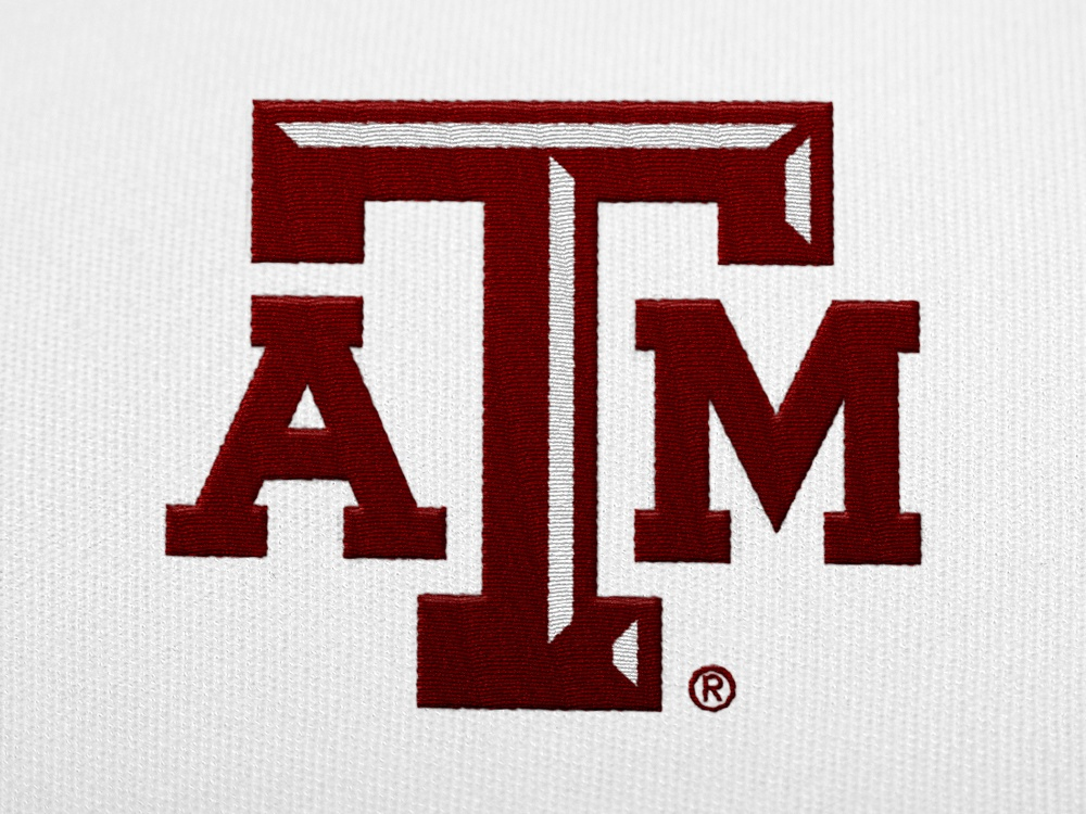 A maroon A&M logo embroidered on a white shirt